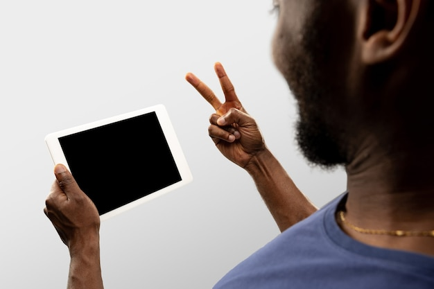 Peace gesture, sign. close up male hands holding smartphone with blank screen during online watching of popular sport matches, championships. copyspace for ad. devices, gadgets, technologies concept.