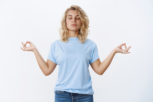 Peace is vital. portrait of calm and relaxed unbothered young woman meditating with closed eyes and focused face standing in lotus pose, search nirvana with mudra signs, practicing yoga