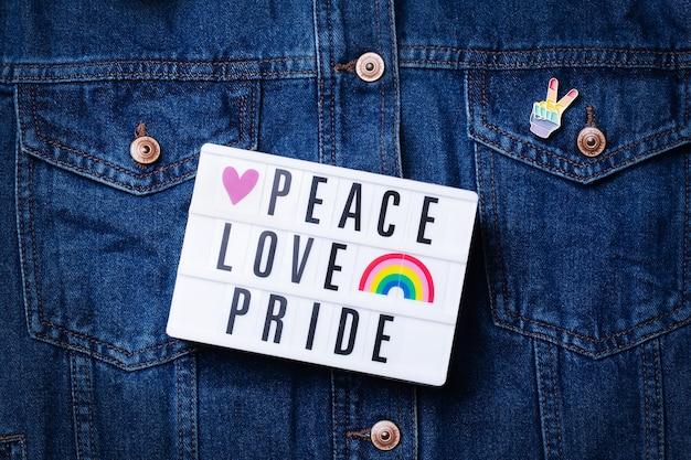 デニムの背景に対して平和愛プライドテキスト虹lgbtqフラグ