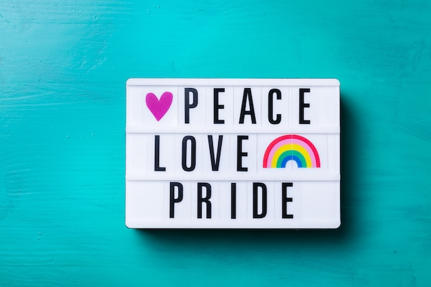 Peace love pride text rainbow lgbtq flag against turquoise background