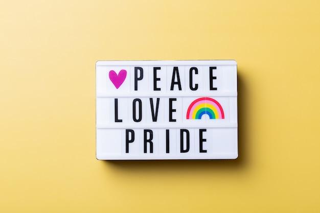 黄色の背景に対して平和愛プライドテキスト虹lgbtqフラグ
