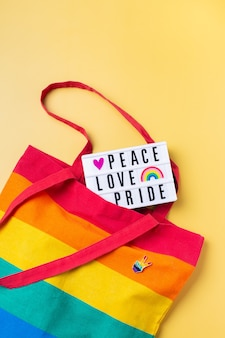 Peace love pride text rainbow reusable bag against yellow background