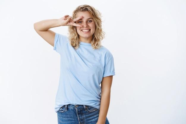 평화를 내 친구. 파란 눈과 짧은 곱슬머리를 한 행복하고 친절하고 귀여운 유럽 여학생의 초상화는 눈에 승리나 디스코 제스처를 보여주고 긍정적으로 웃고 있습니다.