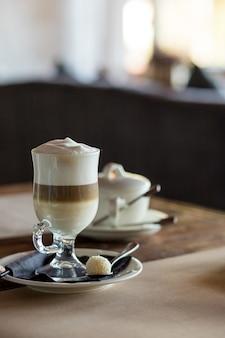 라떼 마끼아또 한잔과 함께 하는 평화의 케이크. 라떼 커피 한 잔과 귀리 쿠키 한 조각. 개념적 맛있는 달콤한 아침 식사. 톤 이미지.
