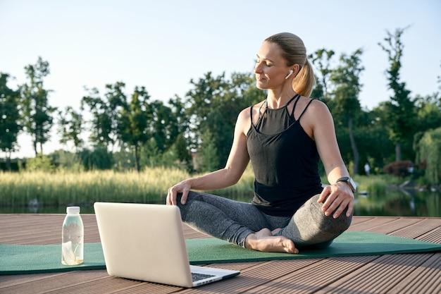 Душевное спокойствие спортивная красивая женщина средних лет смотрит обучающие видео на ноутбуке в то время как