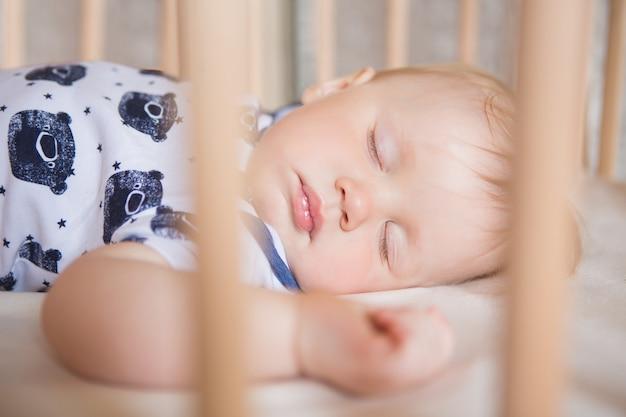 평화롭고 사랑스러운 아기가 방에 있는 침대에서 자고 있습니다. 소프트 포커스입니다. 잠자는 아기 개념. 한 살짜리 아기가 집에서 잔다.