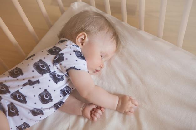 평화롭고 사랑스러운 아기가 방에 있는 침대에서 자고 있습니다. 소프트 포커스입니다. 잠자는 아기 개념. 한 살짜리 아기가 집에서 잔다
