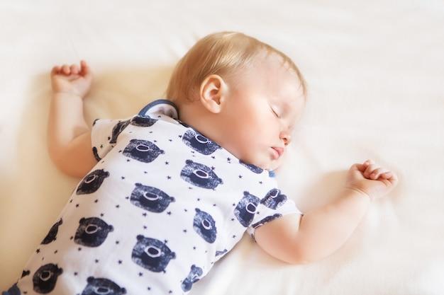 평화롭고 사랑스러운 아기가 방에 흰색 시트를 깔고 침대에서 자고 있습니다. 소프트 포커스입니다. 잠자는 아기 개념. 잠옷 입은 1살 아기, 집에서 잔다