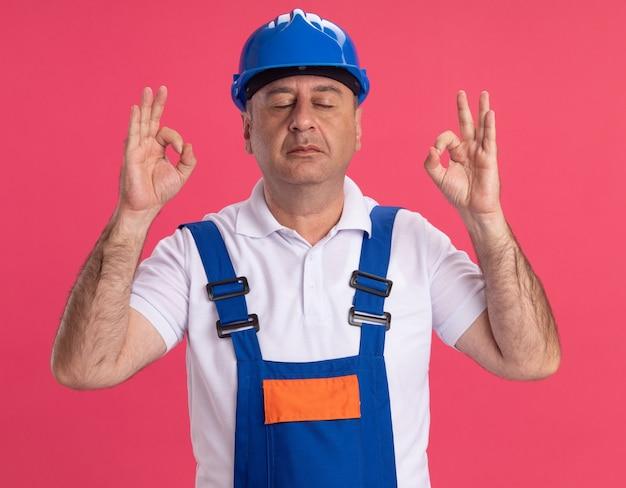 Мирный взрослый кавказский строитель в униформе делает вид, что медитирует на розовом