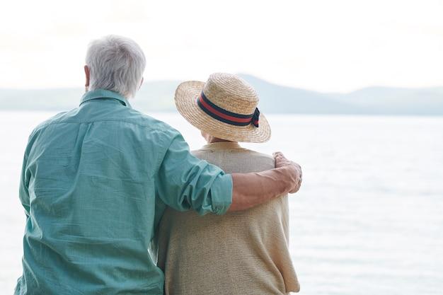 海辺で時間を過ごし、天気と日を楽しんでいるカジュアルウェアの平和でロマンチックな年配のカップル