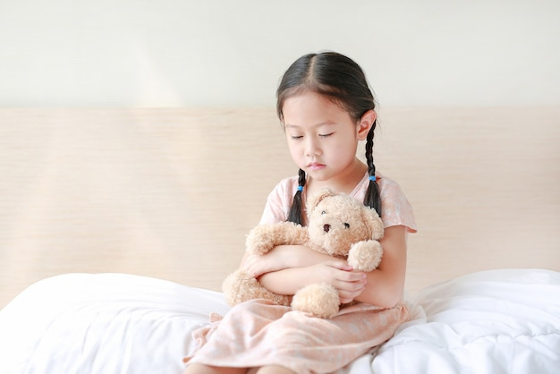Peaceful asian little girl embracing teddy bear while sitting on the bed at home