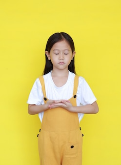 Peaceful asian little girl on yellow background