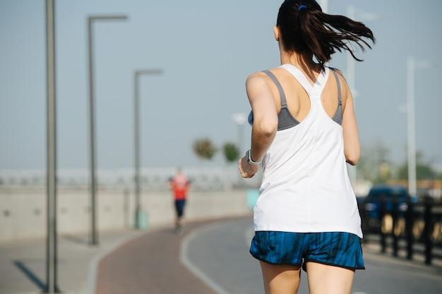 야외에서 새로운 트랙을 달리는 평화로운 운동 여성