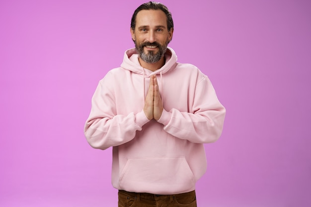 Peaceful attractive bearded mature mail model in trendy pink hoodie press palms together namaste praying gesture smiling delighted relaxed bowing buddhism faith, appreciating help, look thankful.
