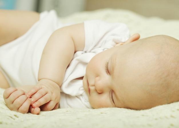Мирный ребенок, лежа на кровати во время сна