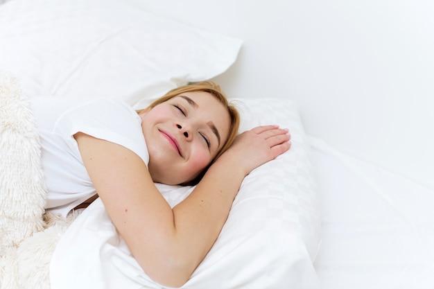 Мирная красивая молодая леди лежа, расслабляясь, спящая в уютной белой кровати на мягкой подушке, покрытой одеялом, наслаждаясь концепцией хорошего здорового сна.