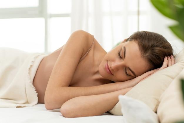 평화로운 아름다운 젊은 여성이 누워 있고, 편안하고, 부드러운 베개에 아늑한 흰색 침대에서 자고 있습니다.