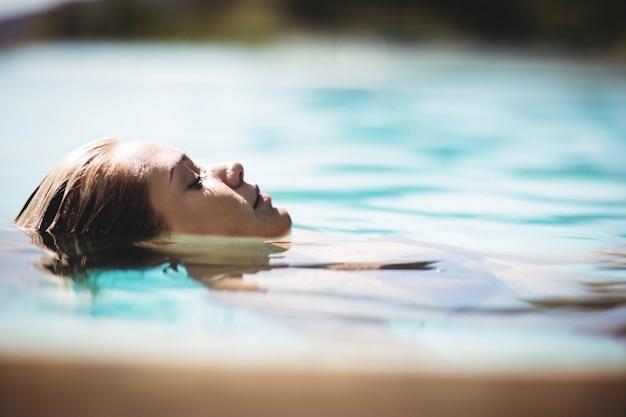 눈을 감고 수영장에 떠있는 평화로운 금발