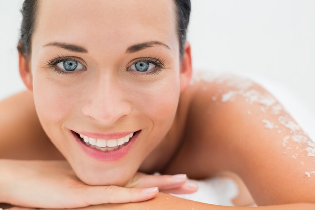 Peaceful brunette lying with salt scrub on back smiling at camera