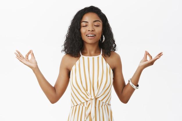 Modello femminile dalla carnagione scura affascinante calma pacifica in salopette a strisce gialle in piedi nella posa del loto