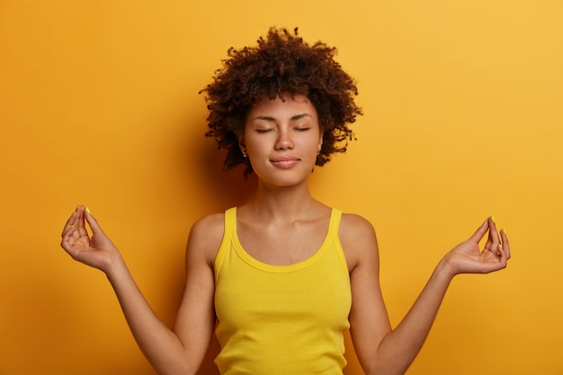 Peaceful calm curly woman stands in lotus pose, reaches nirvana, practices yoga or meditation, keeps eyes shut, dressed in casual wear, isolated over yellow wall, makes okay or zen sign