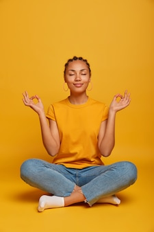 Peaceful calm dark skinned female model sits crossed legs on floor, practices yoga and tries to relax, breathes deeply, closes eyes, reaches nirvana, holds hands sideways, releases stress after work