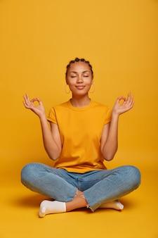 Умиротворенная, спокойная темнокожая модель сидит на полу, скрестив ноги, занимается йогой и пытается расслабиться, глубоко дышит, закрывает глаза, достигает нирваны, держит руки боком, снимает стресс после работы