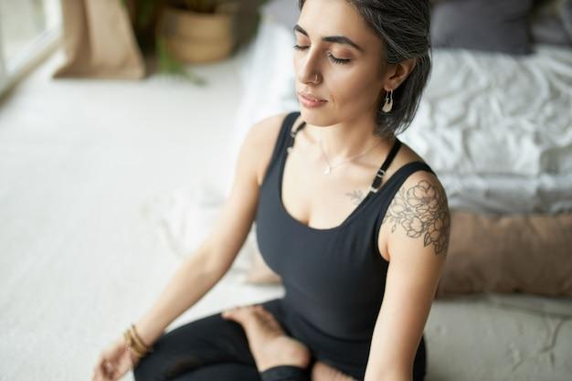 Умиротворенная, спокойная молодая женщина с седыми волосами, носовым кольцом и татуировкой держит глаза закрытыми во время медитации после йоги