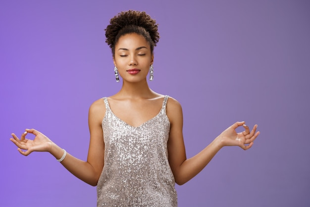 평화롭고 자신감 있는 아프리카계 미국인 젊은 여성 우아한 은색 드레스는 선, 파란색 배경을 찾는 서 있는 너바나 연꽃 요가 자세로 눈을 감고 호흡하는 연습을 진정시킵니다.
