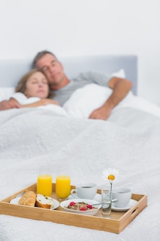 Peaceful couple sleeping with breakfast tray on bed