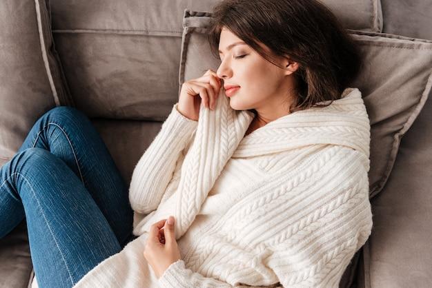 Peaceful cute young woman lying and sleeping on sofa