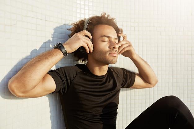 Peaceful dark-skinned sportsman with bushy hairstyle and closed eyes wearing big headphones enjoying music.