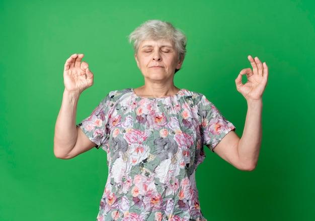 Мирная пожилая женщина делает вид, что медитирует, жестикулируя жестом рукой, двумя руками изолированными на зеленой стене