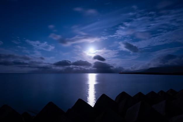 구름 위의 수평선에 떠오르는 평화로운 보름달, 부드러운 바다, 부두의 붉은 빛, 실루엣의 조석 블록.