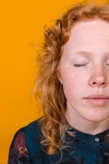 Peaceful ginger young woman with closed eyes