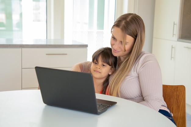 平和な少女と彼女のお母さんはラップトップを使用して、テーブルに座って、ハグ、映画を見て、ディスプレイを見ています。