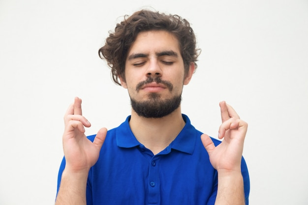 Peaceful guy with closed eyes keeping fingers crossed