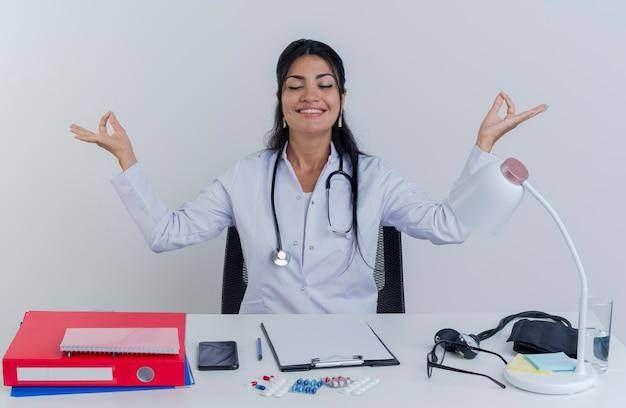 Giovane medico femminile pacifico e felice che indossa veste medica e stetoscopio seduto alla scrivania con strumenti medici meditando con gli occhi chiusi e sorridente isolato