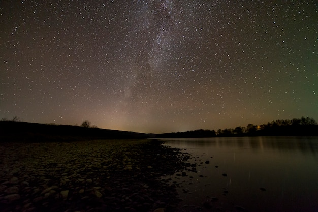 Peaceful landscape panorama at night. long exposure shot of pebbles river bank, trees on horizon, bright stars and milky way galaxy in dark sky reflected in quiet water. beauty of nature concept.