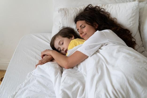 평화로운 사랑의 엄마는 따뜻한 담요 아래 아늑한 침대에서 아이와 함께 자고 있는 취학 전 아들을 껴안습니다.
