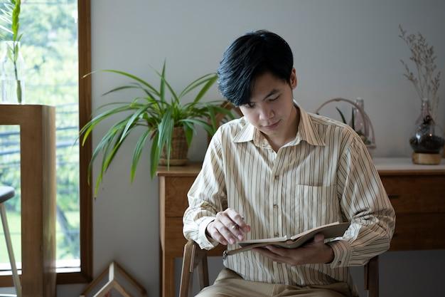 Мирный человек сидит в гостиной и читает книгу.