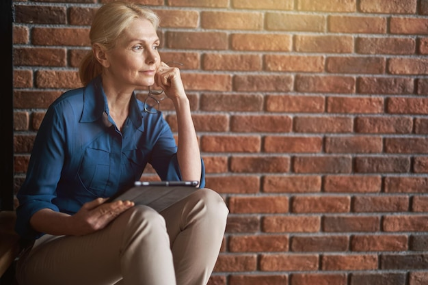 平和な成熟した金髪の白人女性は、前に座っている間、タブレットpcを保持して思慮深く見えます