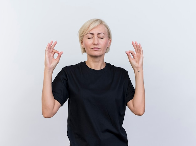 コピースペースと白い背景で隔離の目を閉じて瞑想する平和な中年金髪スラブ女性
