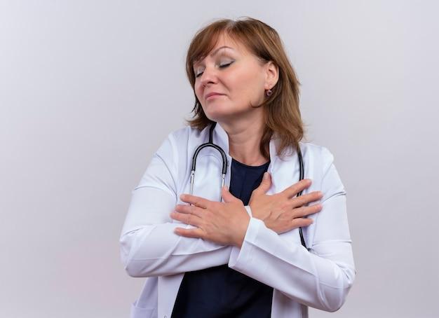 穏やかな中年女性医師医療ローブとコピースペースと孤立した白い壁に目を閉じて胸に手を置く聴診器を着て