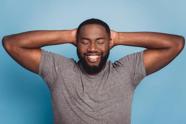 푸른 스튜디오 배경에 고립된 평화로운 밀레니엄 아프리카 남자는 머리 위로 손을 편안하게 해준다