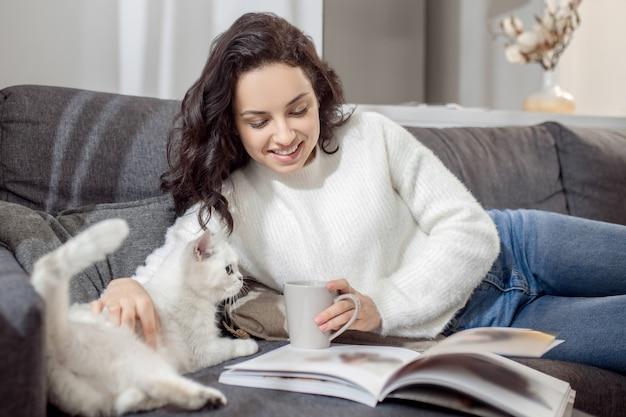 평화로운 분위기. 집에서 쉬고 잡지를 읽고 고양이를 쓰다듬는 여성