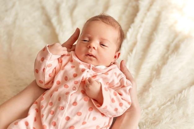 ママの腕に横たわって眠っている平和な新生児、ふわふわの毛布、母性、子供時代の背景に水玉模様の寝台を身に着けているかわいい幼児。