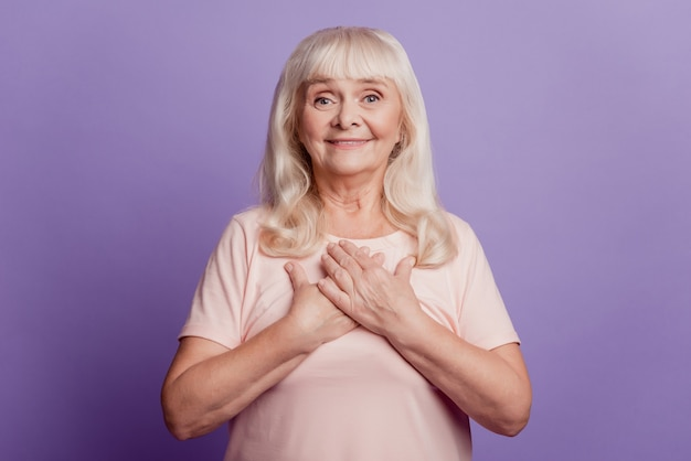 Peaceful old woman put hands chest isolated over violet background