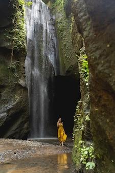 平和な場所。カメラでポーズしながら美しい滝の近くに立っている若い女性のシルエット