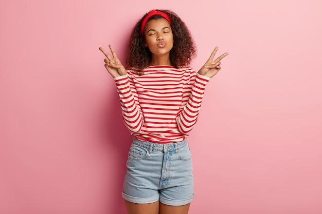 Peaceful pretty beautiful woman with afro hairstyle, keeps lips folded, makes peace gesture with both hands, wears striped jumper and denim shorts